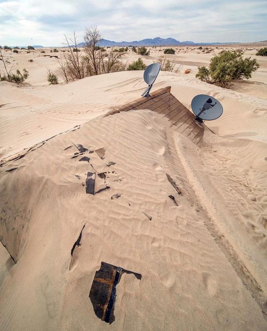 дом засыпанный песком