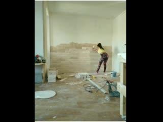 Жена отделывает стену декоративной плиткой под песчанник. Рабочий день в одной м