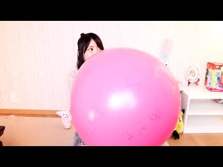 Cute japanese girl inflates a very large pink balloon no pop